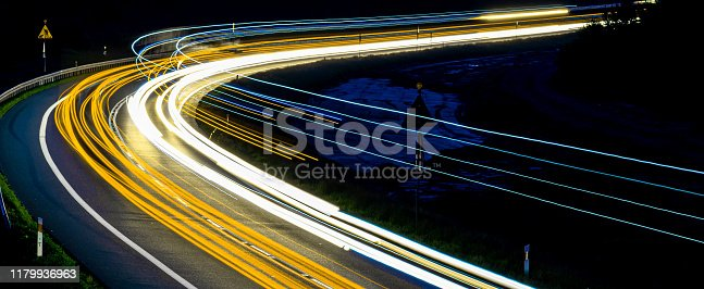 istock lights of cars with night. abstraction of light trails 1179936963