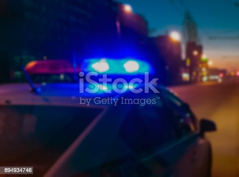 istock Lights of police car in night time, crime scene. Night patrolling the city, lights flashing. Abstract blurry image. 894934746