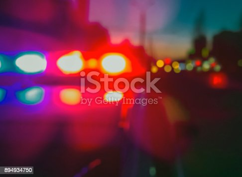 istock Lights of police car in night time, crime scene. Night patrolling the city, lights flashing. Abstract blurry image. 894934750