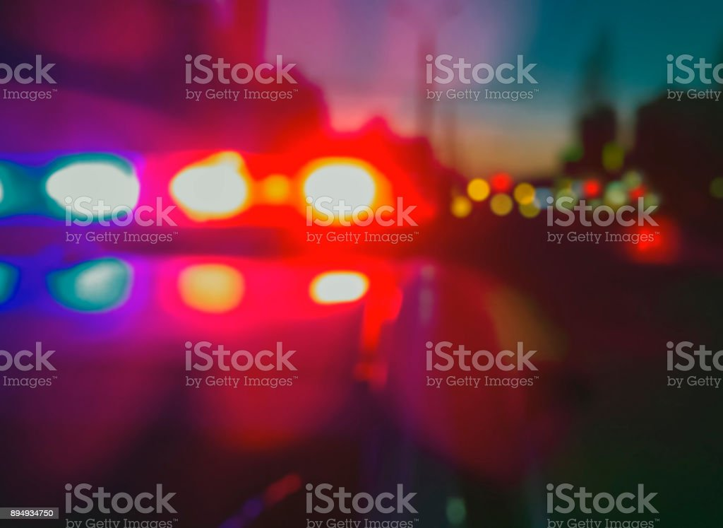 Lights of police car in night time, crime scene. Night patrolling the city, lights flashing. Abstract blurry image. stock photo