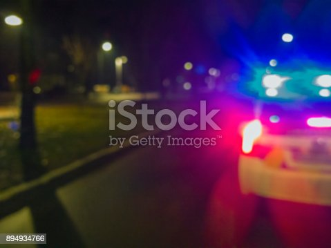 istock Lights of police car in night time, crime scene. Night patrolling the city, lights flashing. Abstract blurry image. 894934766