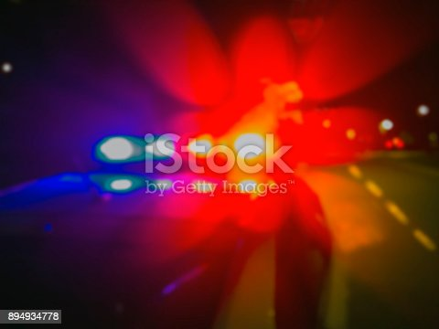 istock Lights of police car in night time, crime scene. Night patrolling the city, lights flashing. Abstract blurry image. 894934778