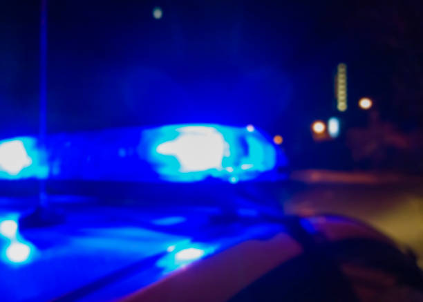 Lights of police car in night time, crime scene. Night patrolling the city, criminal investigation. Abstract blurry image. stock photo
