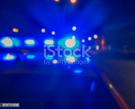 istock Lights of police car in night time, crime scene. Night patrolling the city, criminal investigation. Abstract blurry image. 929701636