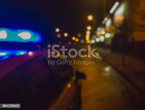 istock Lights of police car in night time. Night patrolling the city. Abstract blurry image. 664209432