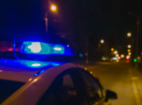 istock Lights of police car in night time. Night patrolling the city. Abstract blurry image. 687987654