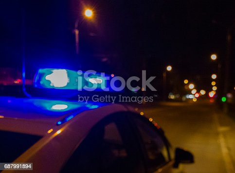 istock Lights of police car in night time. Night patrolling the city. Abstract blurry image. 687991894