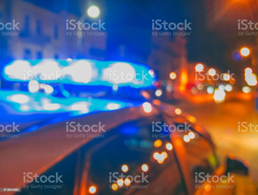 Lights of police car in night time. Night patrolling the city, crime scene. City lights at night background. Abstract blurry image. stock photo