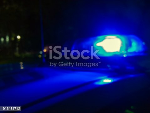904615574 istock photo Lights of police car in night time. Night patrolling the city, crime scene. Abstract blurry image. 913481712