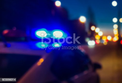 istock Lights of police car in night time. Night patrolling the city. Crime scene. Abstract blurry image for criminal news. 923356314