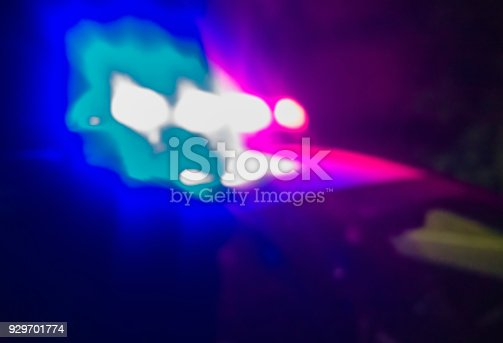 istock Lights of police car in night time. Night patrolling the city. Crime scene. Abstract blurry image. 929701774