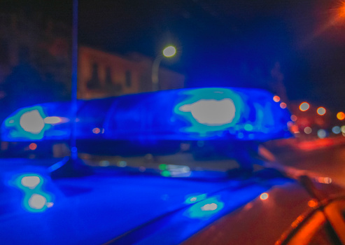 istock Lights of police car in night time. Night patrolling the city, lights flashing. Abstract blurry image. 890157514