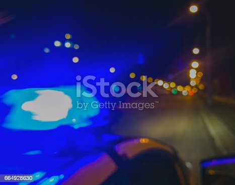 istock Lights of police car in night time. Night patrolling the city. 664928630