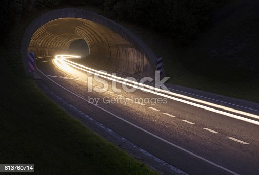 istock Lights of the car on the road to the tunnel. 613760714