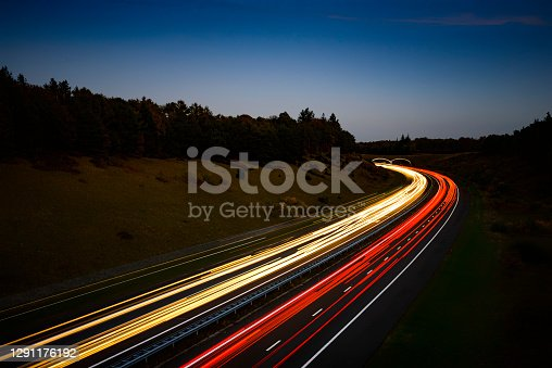 Lights of traffic passing by on a highway through nature at night. Long exposure image with light trails in white and red caused by the head and tail lights of the passing cars.