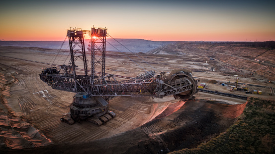 Aerial shot of a giant open pit lignite mine Hambach in Germany. Large bucket excavator mining machinery. Moody light at sunset.