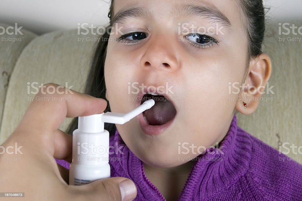 liitle girl using throat spray royalty-free stock photo