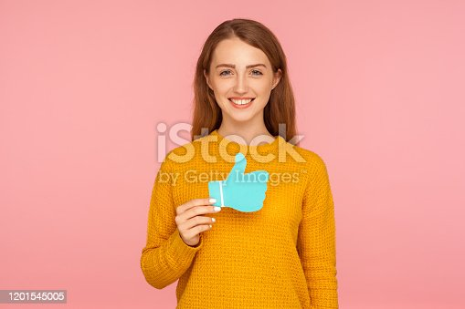 640248524 istock photo Like and share! Portrait of beautiful happy red hair girl in sweater holding blue thumb up love icon and smiling 1201545005