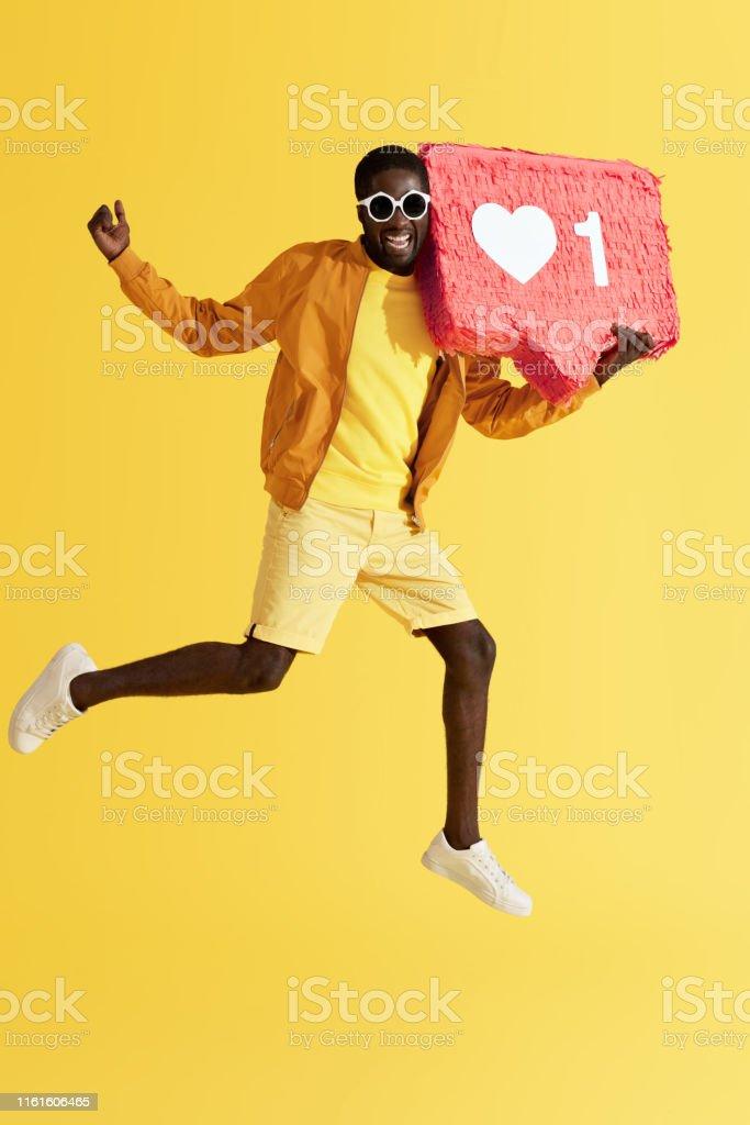Like. Cheerful man jumping with social media like icon pinata on...
