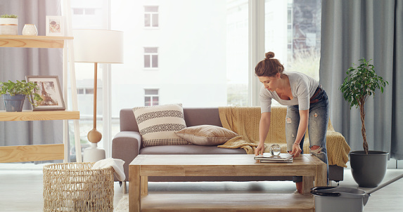 Shot of a young woman cleaning her living room
