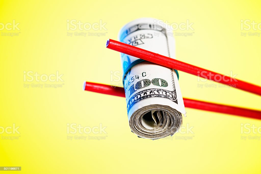 Like expensive sushi, chopsticks lift roll of hundred-dollar bills stock photo