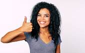 istock I like it. Front portrait of young good-looking ethnic Afro girl smiling broadly and showing thumbs up with her right hand. 1180642202