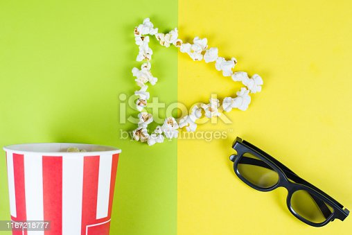istock I like love adore watching new film concept. Top above high angle overhead close up view bright photo of play button with tasty popcorn and black 3d glasses isolated over two parts halves background 1167218777