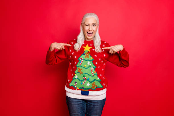 I like my jumper concept. Photo of blinking grey-haired positive hinting cheerful nice granny showing you her best with small pompons gingerbread men decor pullover isolated bright color background I like my jumper concept. Photo of blinking grey-haired positive hinting, cheerful nice granny showing you her best with small pompons gingerbread men decor pullover isolated bright color background ugliness stock pictures, royalty-free photos & images