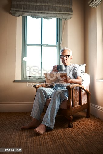 Full length shot of a senior man sitting and reading a newspaper while holding a cup of coffee at home