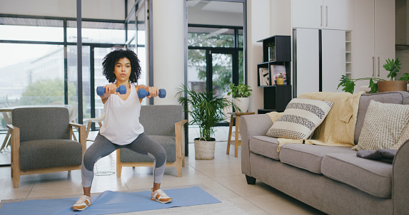 Shot of a young woman exercising with dumbbells at home