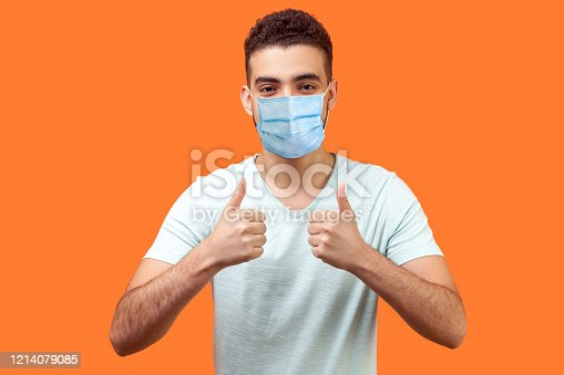 Like! Portrait of optimistic handsome man with medical mask in white t-shirt showing thumbs up gesture and smiling, meaning well done, good job. indoor studio shot isolated on orange background