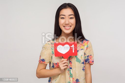 640248524 istock photo Like social network content! Beautiful happy blogger girl in blouse showing internet heart icon, recommending to subscribe 1208160322