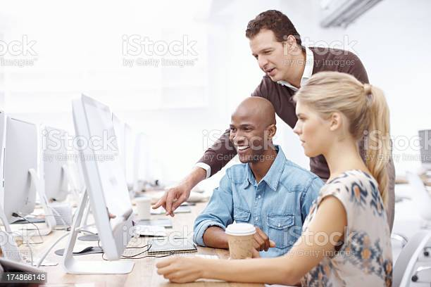 Two colleagues hard at work while their boss looks on in agreement