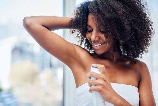 Shot of a woman spraying deodorant on her underarms