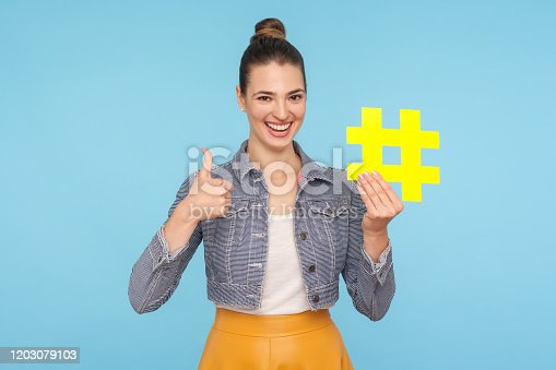 640248524 istock photo Like to popular blog and trends. Joyful attractive woman with hair bun in stylish outfit holding big yellow hashtag symbol 1203079103