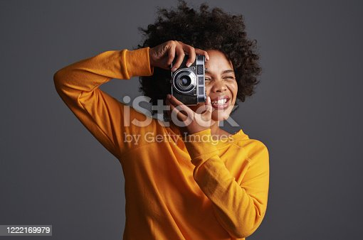 Shot of a young woman taking pictures on a vintage camera against a grey background