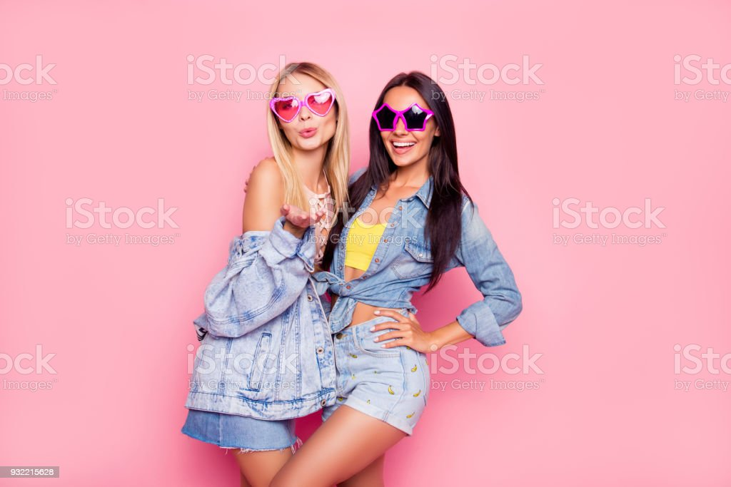 I like you! Beautiful playful cheerful women dressed in fashionable stylish shorts, shirt, jacket, top, funny star and heart glasses are embracing, sending air-kiss, isolated on bright pink background royalty-free stock photo