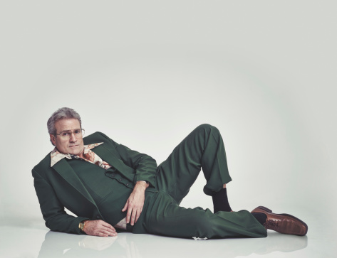 Studio shot of a mature man in a retro suit lying down and striking a pose