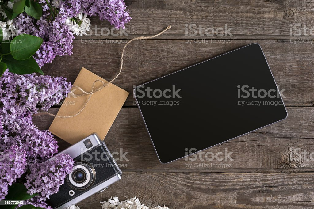 Lilac blossom on rustic wooden background, tablet with empty space for greeting message. Scissors, thread reel, small envelope. Top view royalty-free stock photo