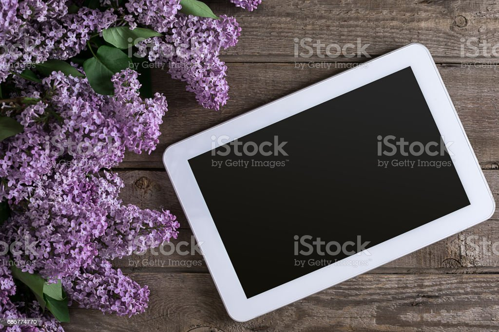 Lilac blossom on rustic wooden background, tablet with empty space for greeting message. Top view royalty-free stock photo