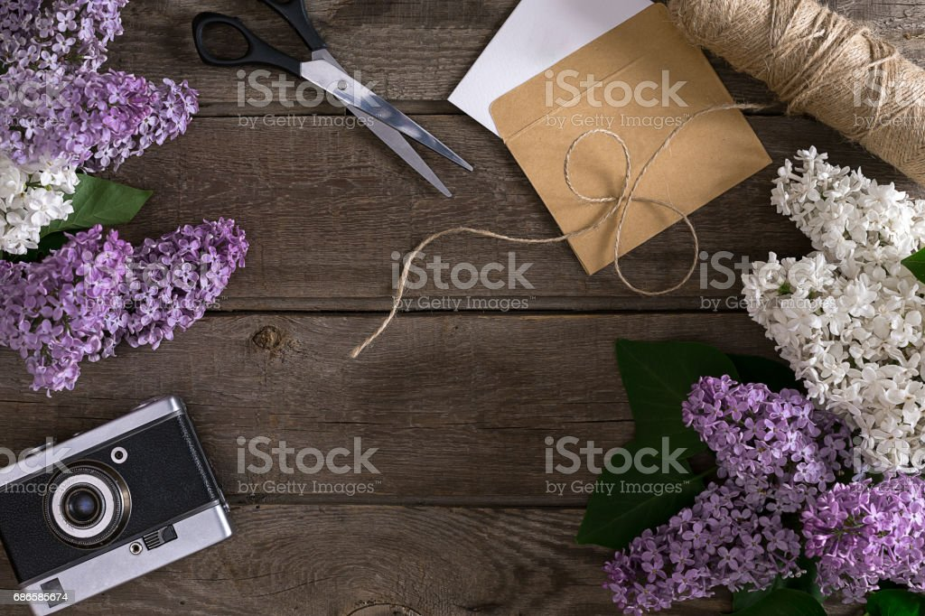 Lilac blossom on rustic wooden background with empty space for greeting message. Scissors, thread reel, small envelope. Top view royalty-free stock photo