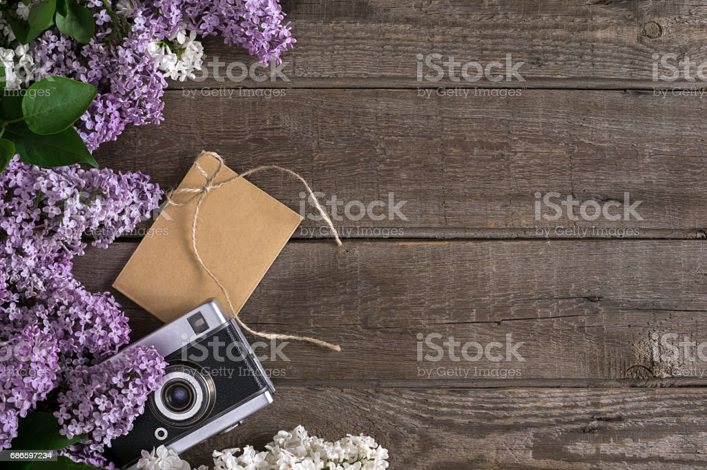 Lilac blossom on rustic wooden background with empty space for greeting message. Camera, small envelope. Top view royalty-free stock photo