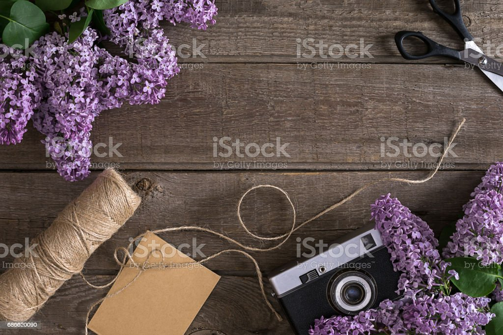 Lilac blossom on rustic wooden background with empty space for greeting message. Scissors, thread reel, small envelope and camera. Top view royalty-free stock photo