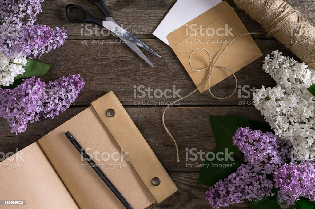 Lilac blossom on rustic wooden background with notebook for greeting message. Top view photo libre de droits