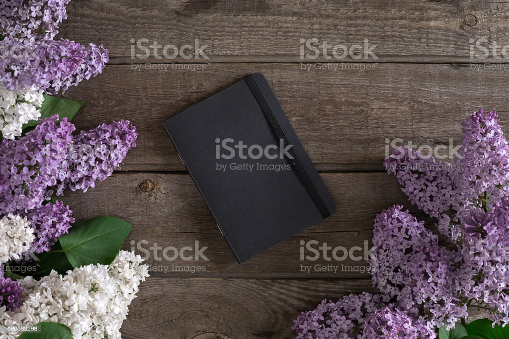 Lilac blossom on rustic wooden background with notebook for greeting message. Top view royalty-free stock photo