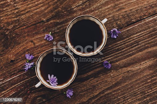Lilac chicory flowers and cups on vintage wooden table. Flat lay, copy space. Natural coffee substitute.
