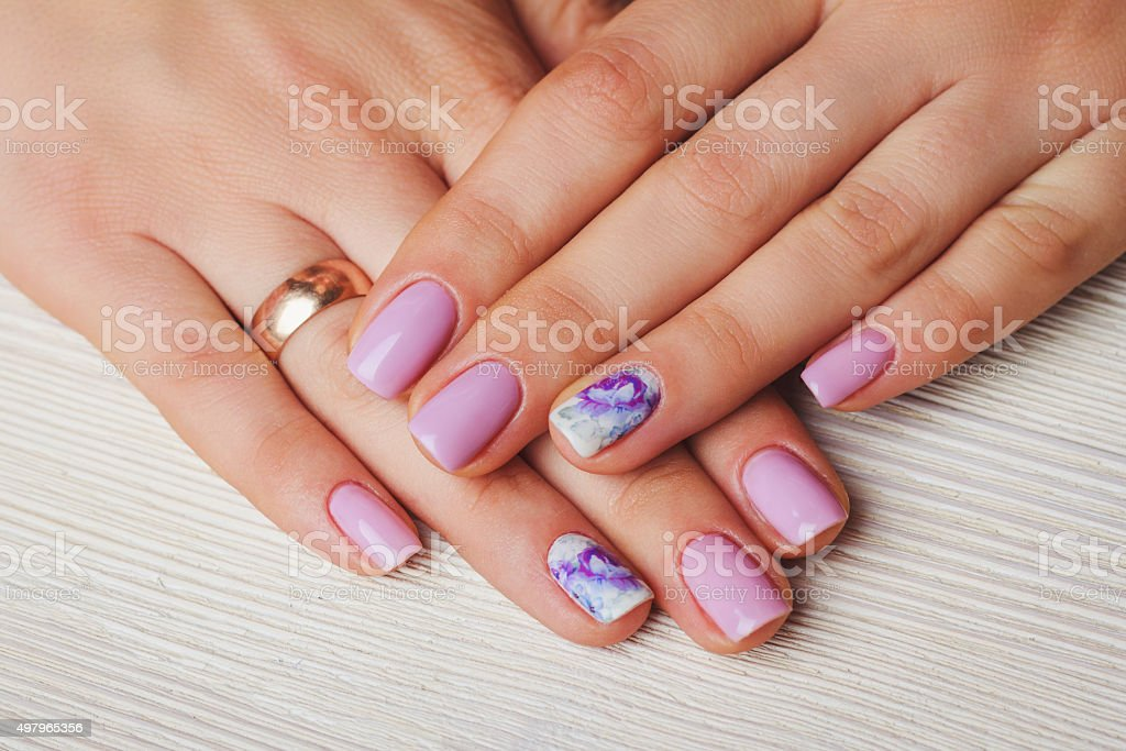 Lilac nail art with printed flowers on light background stock photo