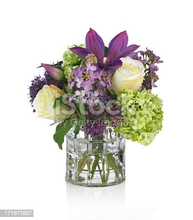 A beautiful springtime arrangement of flowers in a windowpane glass vase. The bouquet contains roses, clematis, hydrangea and lilac. Shot against a bright white background. There is a path which may be used to delete the reflection if desired. Extremely high quality faux flowers.