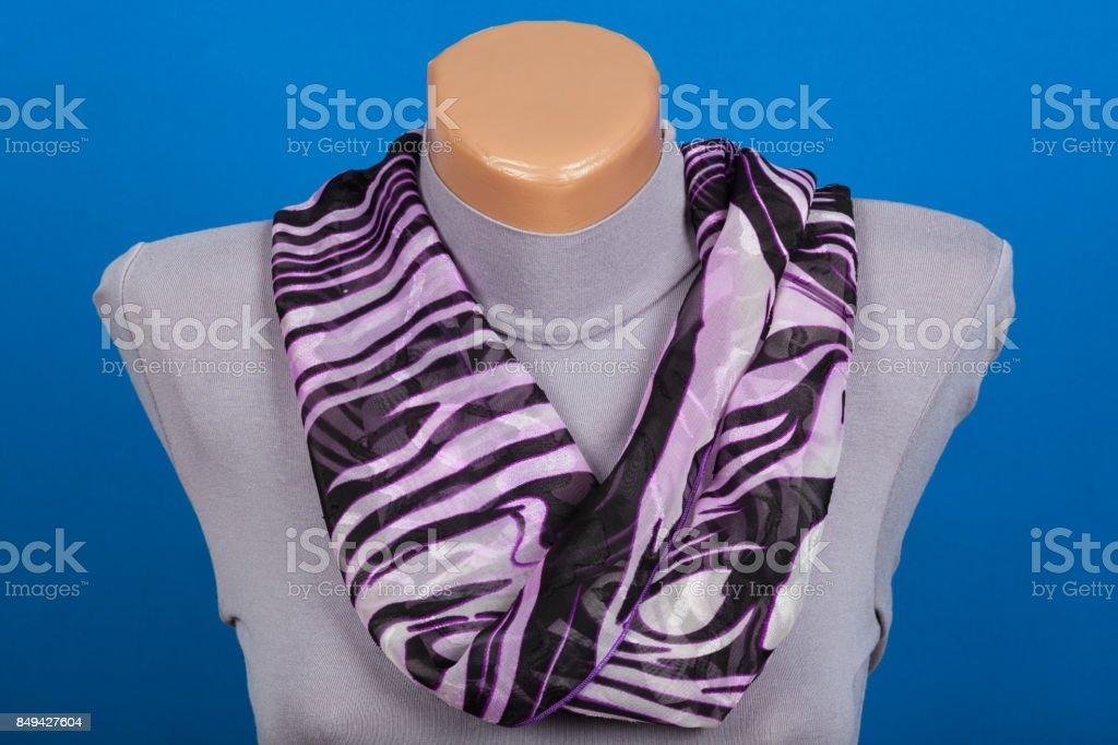 Lilac scarf on mannequin isolated on blue background stock photo