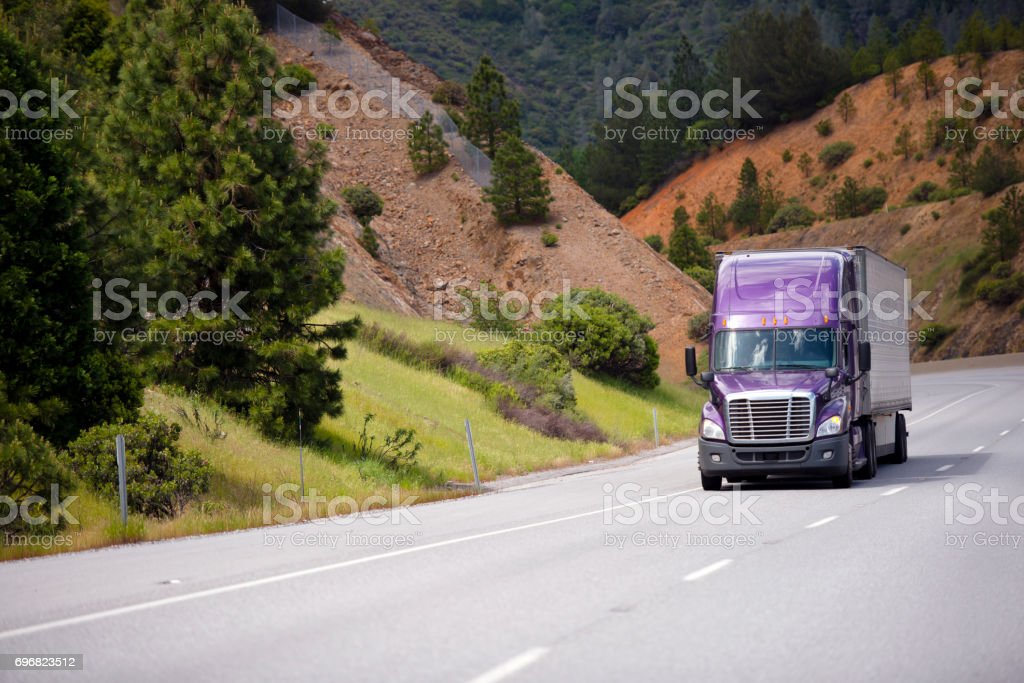 Lilac semi truck with aluminum trailer is moving along winding highway through the pass in California against the background of orange mountain slopes stock photo